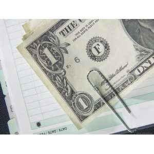 American Dollar Bill Paper Clipped to Accounting Book Photographic